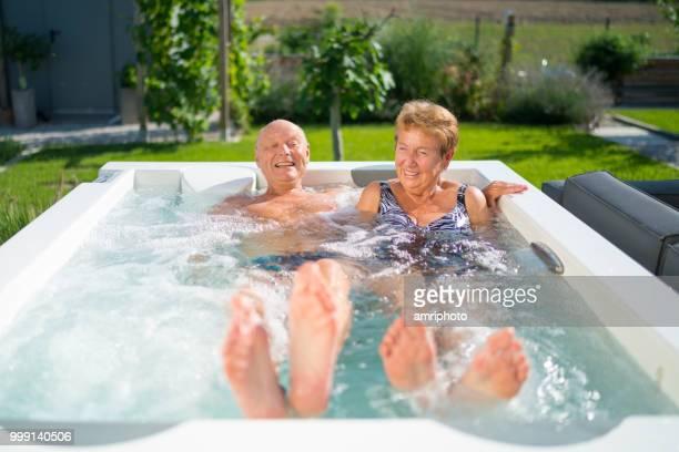 70 jaar oude senior paar samen ontspannen in hete buis in tuin