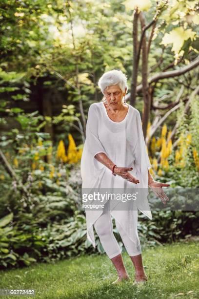 84 jaar oude senior vrouw doet tai chi - 80 89 jaar stockfoto's en -beelden