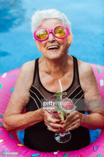 84 years old senior woman in the pool - disruptagingcollection stock photos and pictures