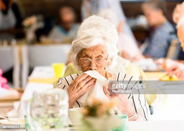105 years old senior woman using a napkin during lunch - 100th anniversary stock pictures, royalty-free photos & images