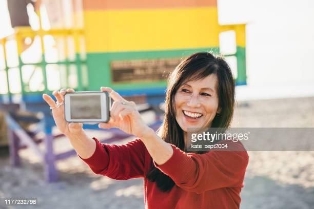 64 anos de idade mulheres sênior que tomam o selfie na praia - 60 64 anos - fotografias e filmes do acervo