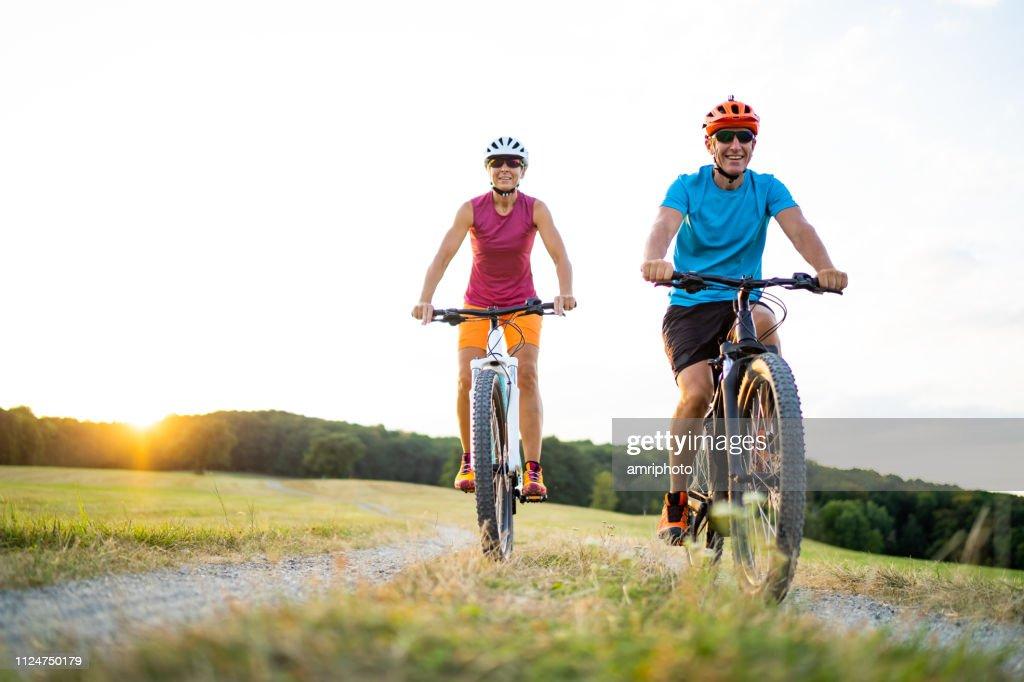 40-50 jaar oud sportief paar fietsen op elektrische mountainbikes in landelijke omgeving : Stockfoto