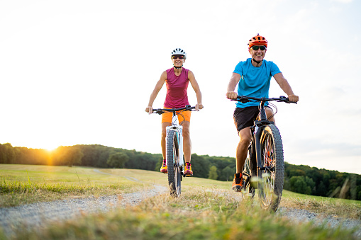 40-50 years old sporty couple cycling on electric mountain bikes in rural environment 1124750179