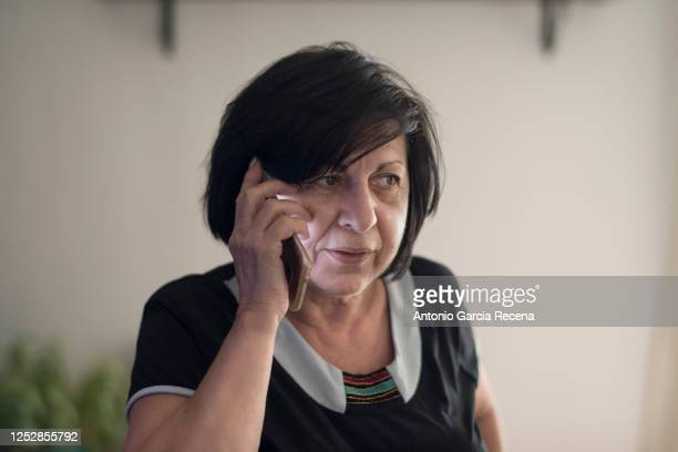 65 years old woman at phone talking at home - 65 69 years stock pictures, royalty-free photos & images