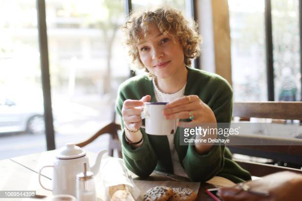 A 40 years old woman drinking a cup of tea in a parisian cafe