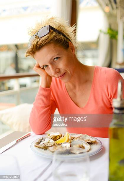 40 years old woman in restaurant with plate of oysters