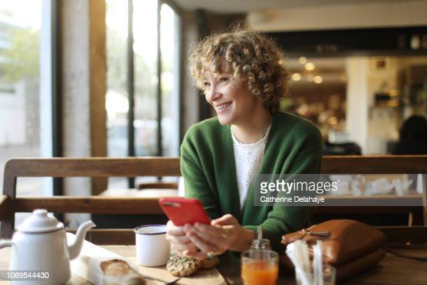 A 40 years old woman looking at her cell phone in a parisian cafe