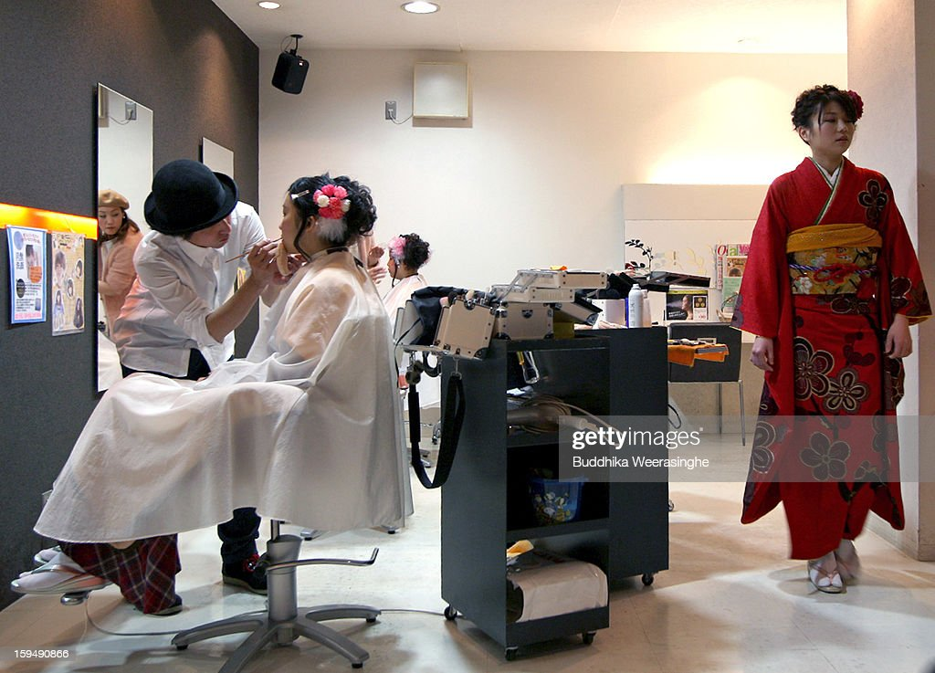 20 years old women get make-up as woman dressed in kimono walks beside after finished her fitting for their 'Coming-of-Age Day' celebration at Hair Sakura beauty parlor on January 14, 2013 in Himeji, Japan. The event involves 20-year-old Japanese people celebrating their eligibility to drink alcohol, smoke and vote.