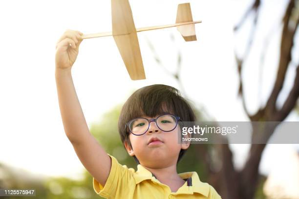 5 years old young boy throwing toy aeroplane. - 4 5 years stock pictures, royalty-free photos & images