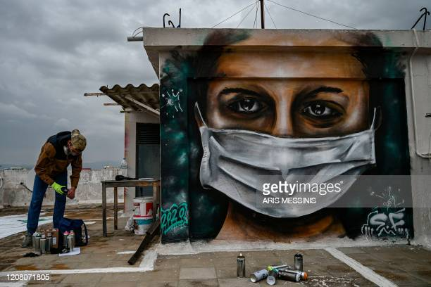 16 years old youth artist SF paints a mural about the COVID19 crisis on the roof of his building in Athens on March 23 2020 / RESTRICTED TO EDITORIAL...