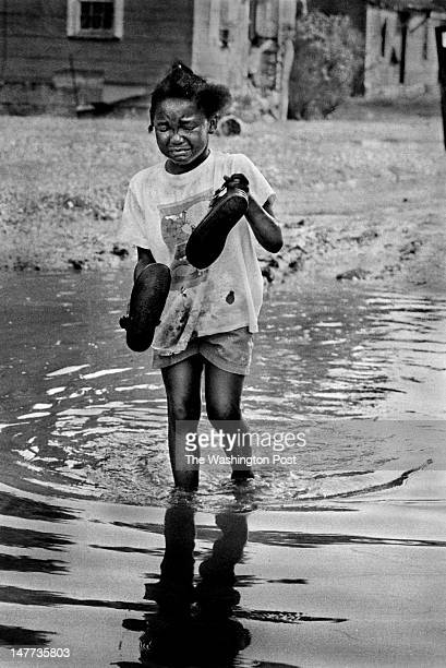 FILE Yecenia Lockwood is in tears as she wades through the water that covers the unpaved streets in Bayview Virginia on June 15 1998 She had just...