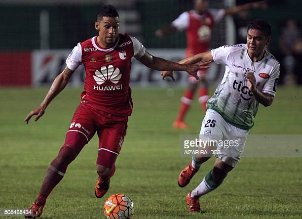 Yeison Gordillo of Colombian team Independiente Santa Fe drives the ball past Joel Bejaranode of Bolivia's Oriente Petrolero during their...
