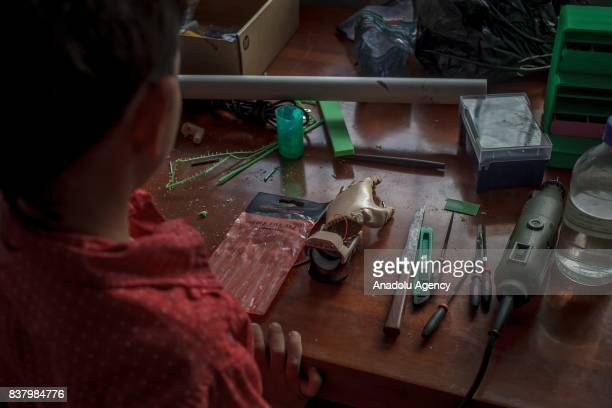 Yeisson Villanueva looks his newly designed 3D printed hand at Foundation of Materialization 3D in Bogota Colombia August 08 2017 A group of...
