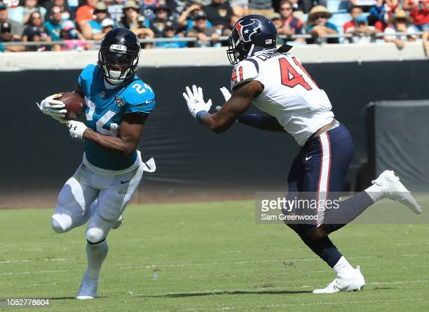 J Yeldon of the Jacksonville Jaguars attempts to run past Zach Cunningham of the Houston Texans during the game at TIAA Bank Field on October 21 2018...