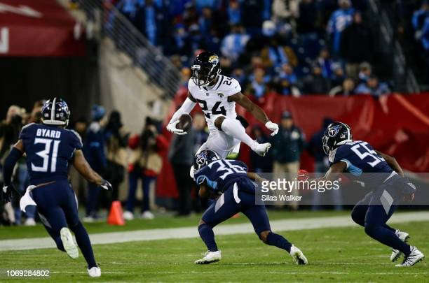 Yeldon of the Jacksonville Jaguars leaps over LeShaun Sims of the Tennessee Titans while running with the ball during the first quarter at Nissan...