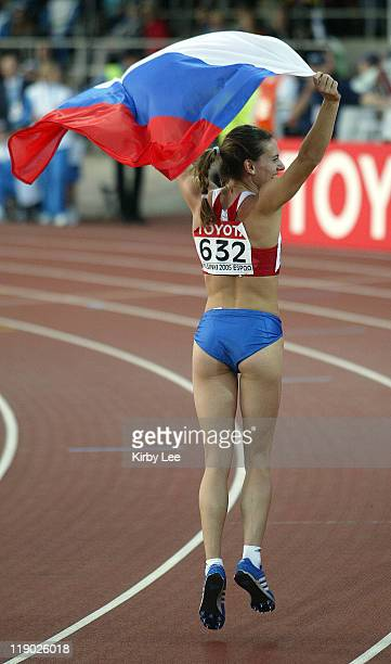 Yelena Isinbayeva of Russia takes a victory lap with flag after wining the women's pole vault with a worldrecord clearance of 165 1/4 in the IAAF...