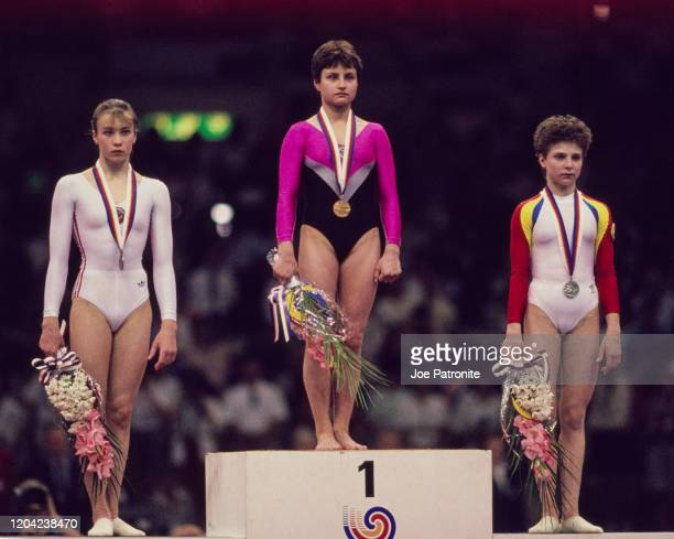 Yelena Shushunova of the Soviet Union stands on the top step of the podium with her gold medal with silver medallist Daniela Silivas of Romania and...