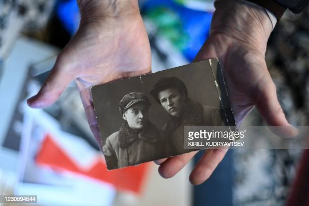 Yelizaveta Mikhaylova, a daughter of a victim of Stalinist repressions, shows a photo of her parents - father Semyon and mother Antonina - at her...