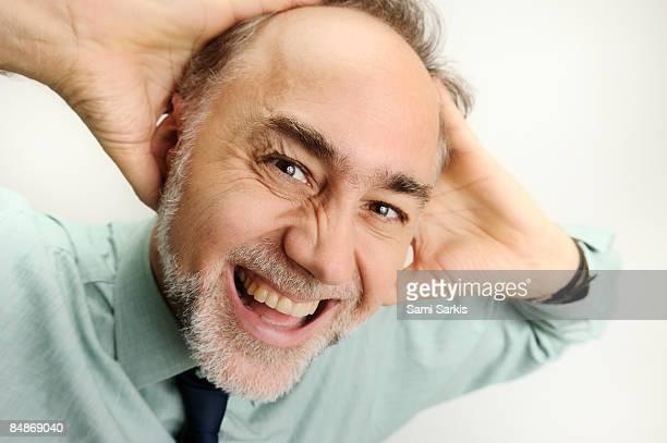 Yelling mature business man, having headache,
