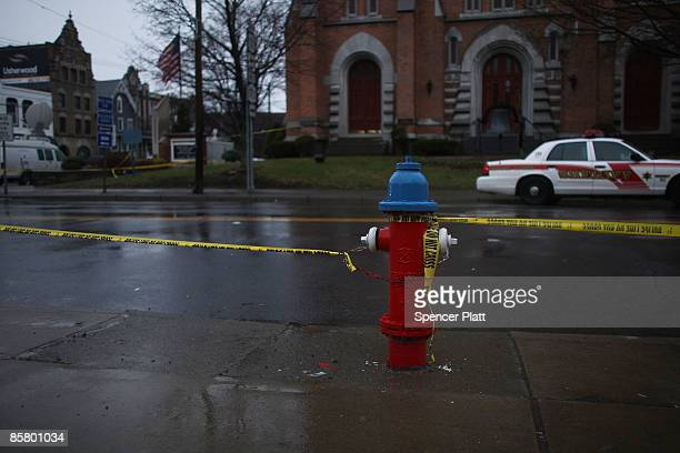 Yello police tape marks the street beside the site where a gunman killed 13 people in an immigration community center yesterday April 4, 2009 in...