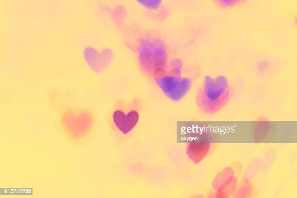 yellow abstract background with violet and pink heats bokeh - heart background stock pictures, royalty-free photos & images