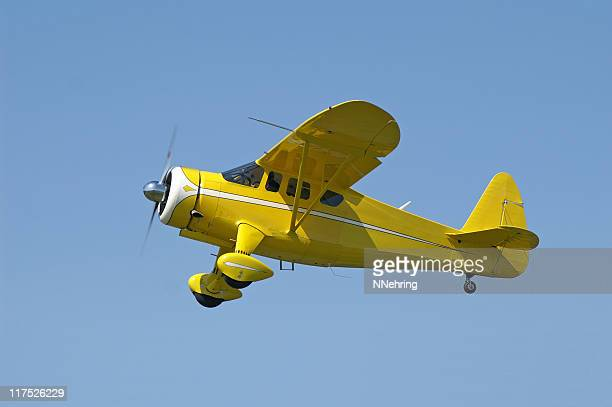 yellow airplane Howard Aircraft DGA15P flying in clear blue sky