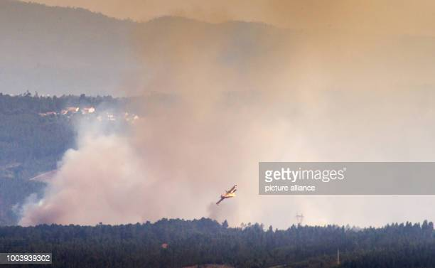 A yellow airtanker circles over a forest fire near Derreada Cimeira a town around 180 kilometres northeast of Lisbon Portugal 19 June 2017 A deadly...