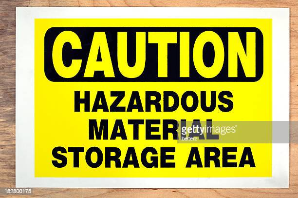 Yellow and black caution sign on wooden wall