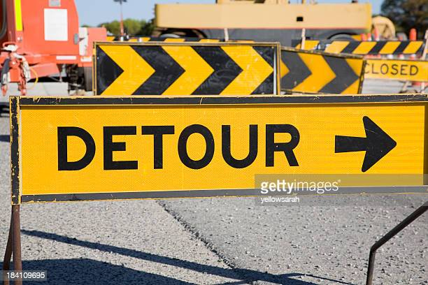 Yellow and black detour sign on the road