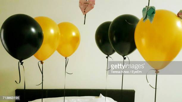 Yellow And Black Helium Balloons Against White Wall