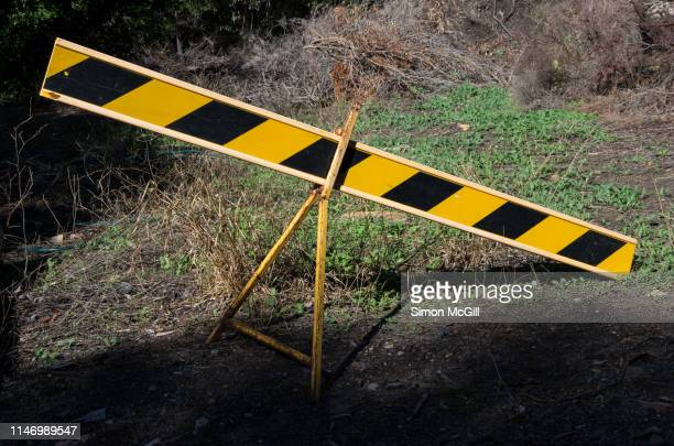 yellow and black striped road traffic barricade on a vacant lot - barricade stock pictures, royalty-free photos & images