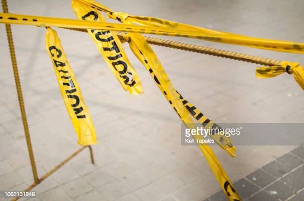 yellow and black tape caution sign - mord stock-fotos und bilder