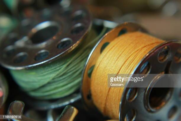 yellow and green thread bobbins - embroidery stock pictures, royalty-free photos & images