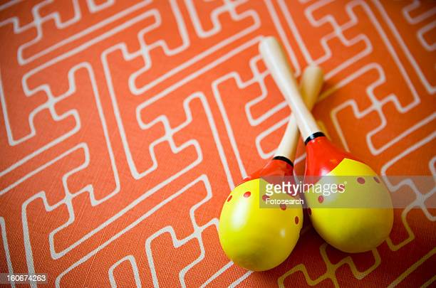 Yellow and red maracas on orange patterned background
