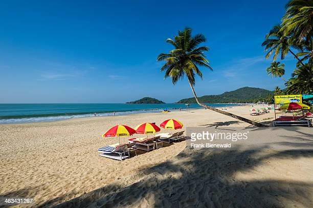 Yellow and red sun shades at Palolem Beach with blue sky palm trees white sand and blue sea
