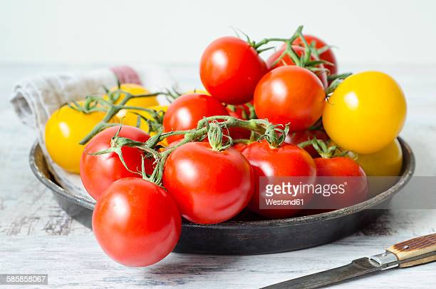 Yellow and red tomatoes with a knife on a wooden board