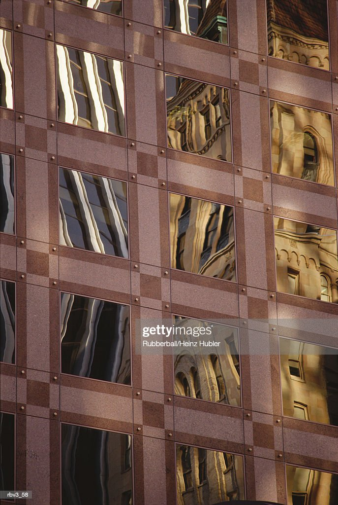 yellow and white buildings are reflected in the glass windows of a maroon building : Foto de stock