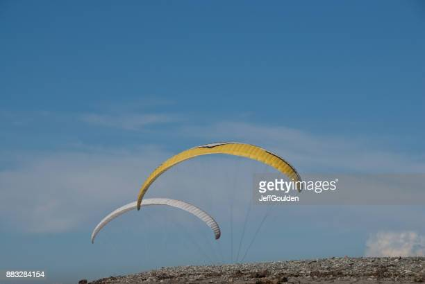Two Paragliders Flying Above the Beach