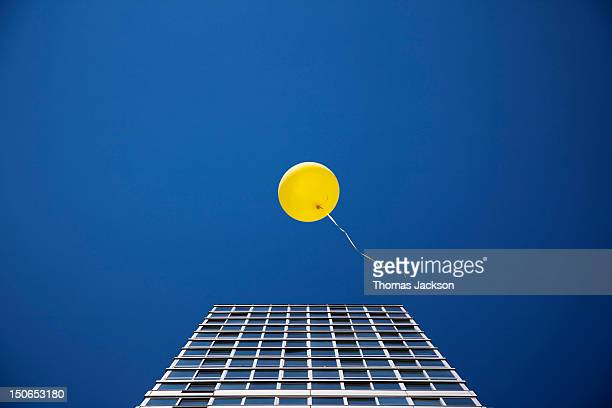 Yellow balloon floating past single skyscraper