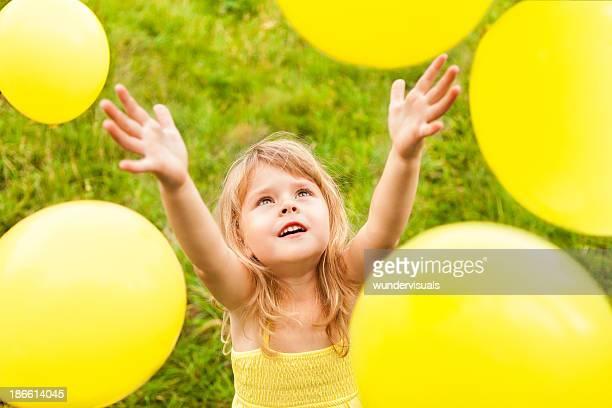 Yellow Balloons Around Little Girl