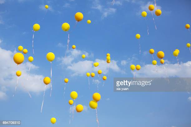 Yellow balloons floating in blue sky