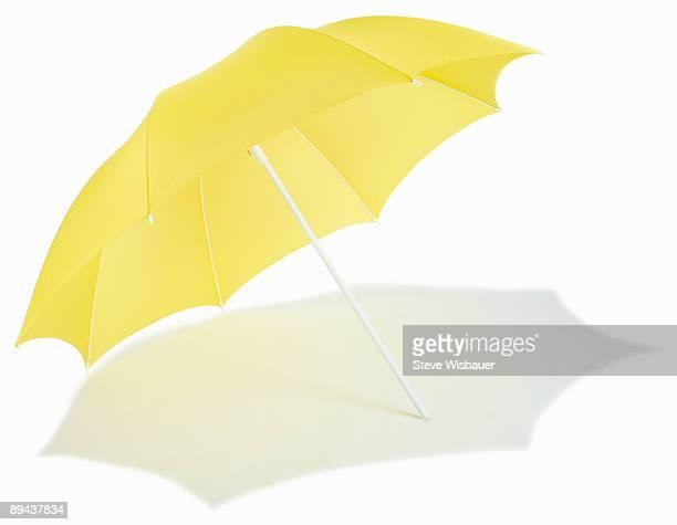 Yellow beach umbrella open with shadow