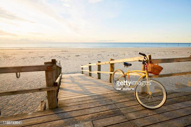 yellow beachcruiser bicycle leaning at a railing at an empty beach during sunrise - north sea stock pictures, royalty-free photos & images