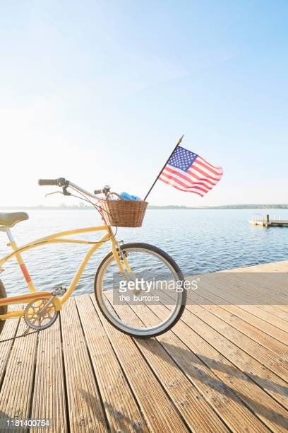 yellow beachcruiser bicycle with united states flag blowing in the wind on a jetty at an idyllic lake in summer against blue sky - independence day stock pictures, royalty-free photos & images