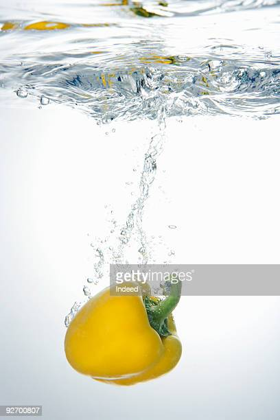 Yellow bell pepper sinking into water