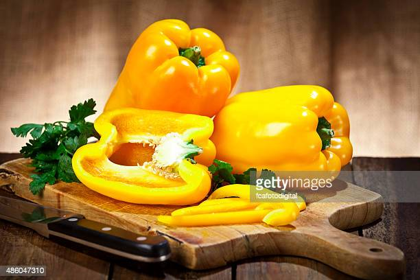 yellow bell peppers on wooden cutting board - yellow bell pepper stock pictures, royalty-free photos & images