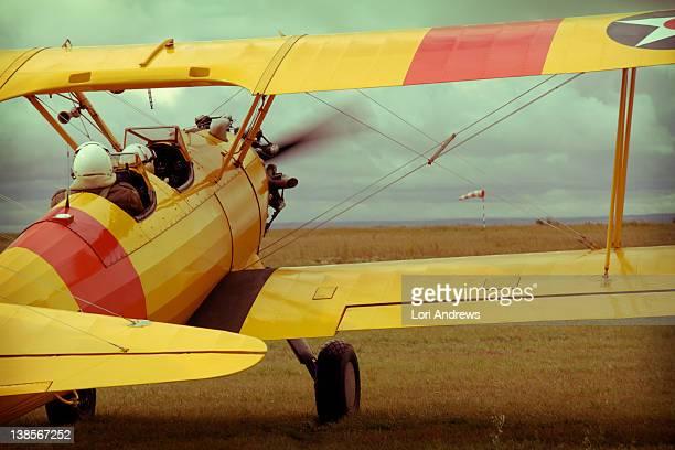 Yellow bi plane takes off