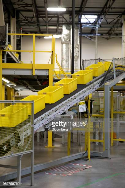 Yellow bins move up a conveyor belt at the Amazoncom Inc fulfillment center in Robbinsville New Jersey US on Thursday June 7 2018 Seattlebased Amazon...
