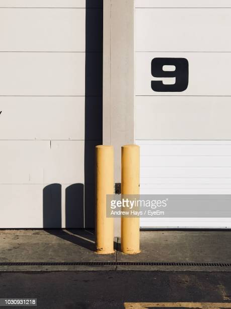 yellow bollard against white wall - bollard stock photos and pictures