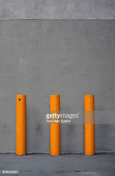 yellow bollards against concrete wall - bollard stock photos and pictures